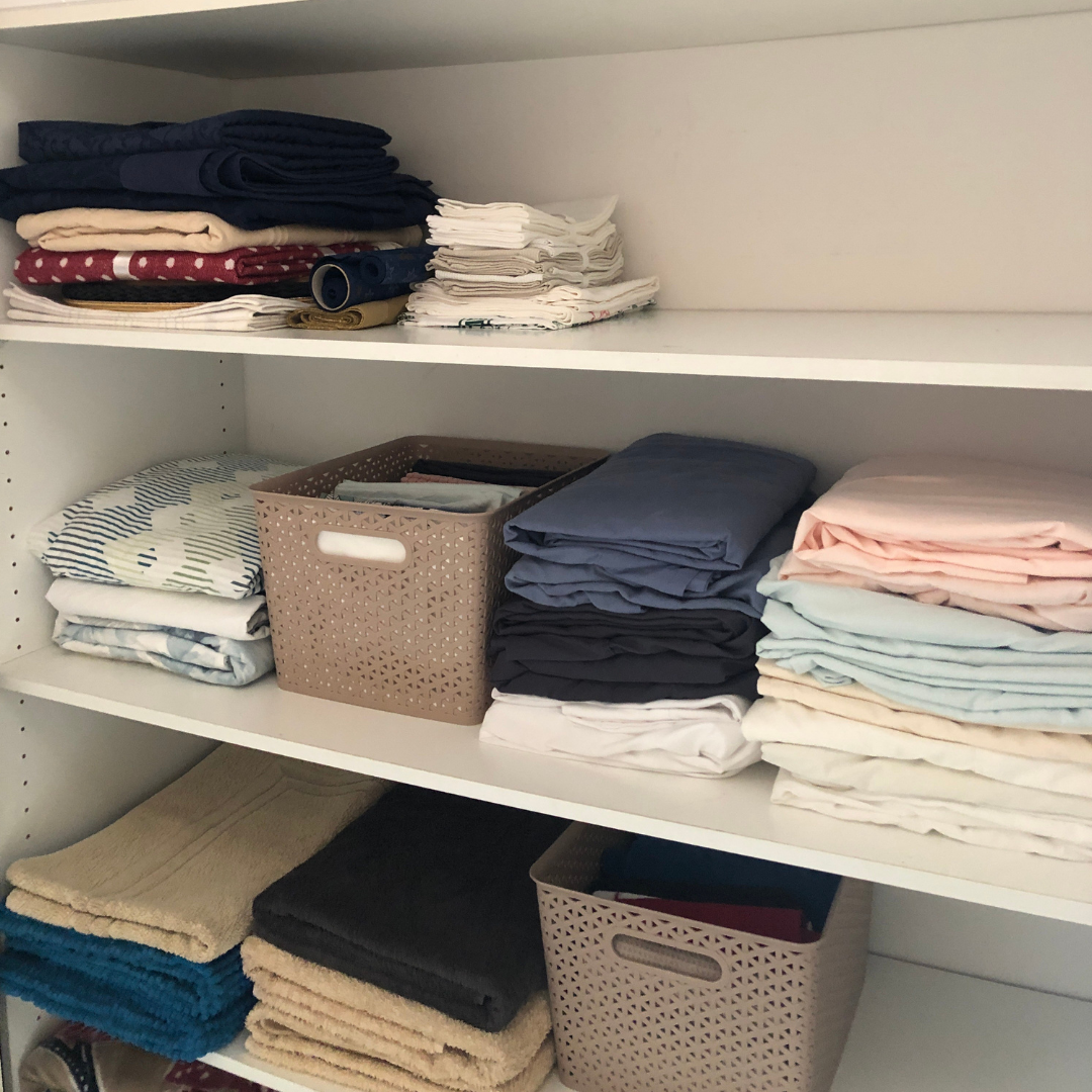 Linen closet with neatly folded fitted sheets on shelf