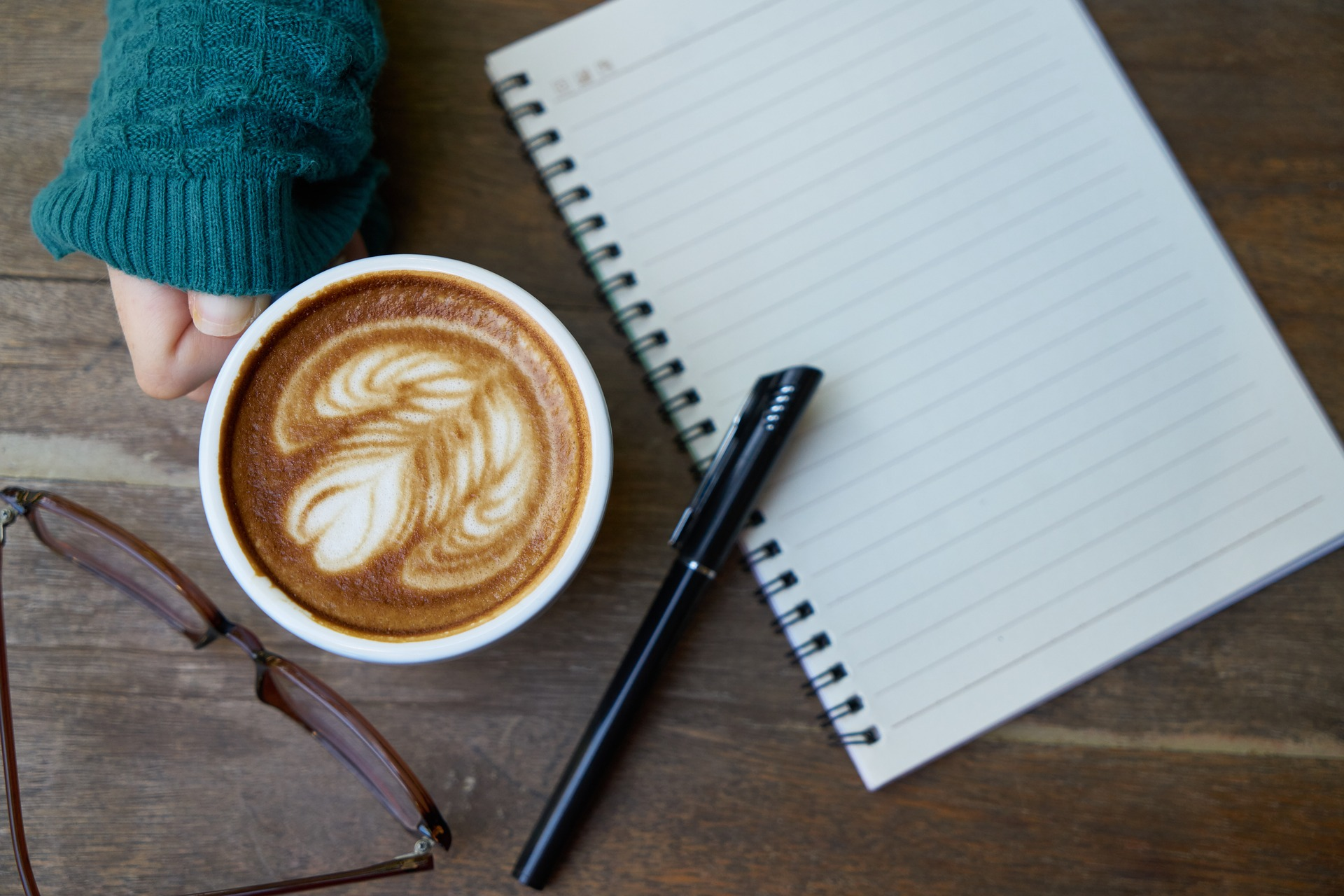coffee cup, pen, journal, and eyeglasses