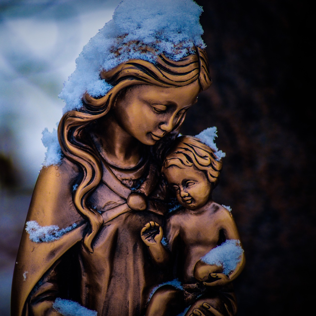 bronze statue of Mary holding baby Jesus, both covered in snow
