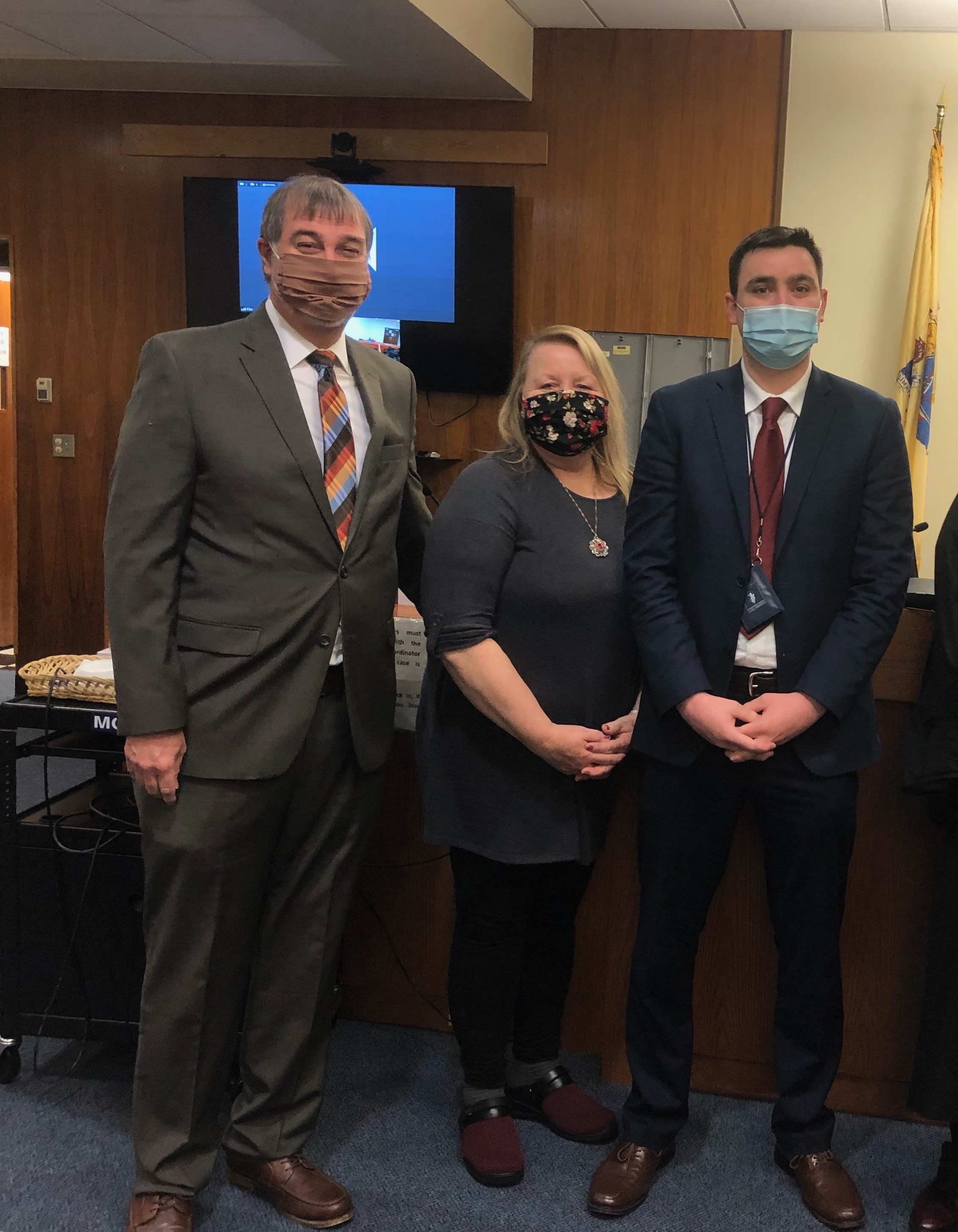 Father, mother, adult son standing together, all wearing masks