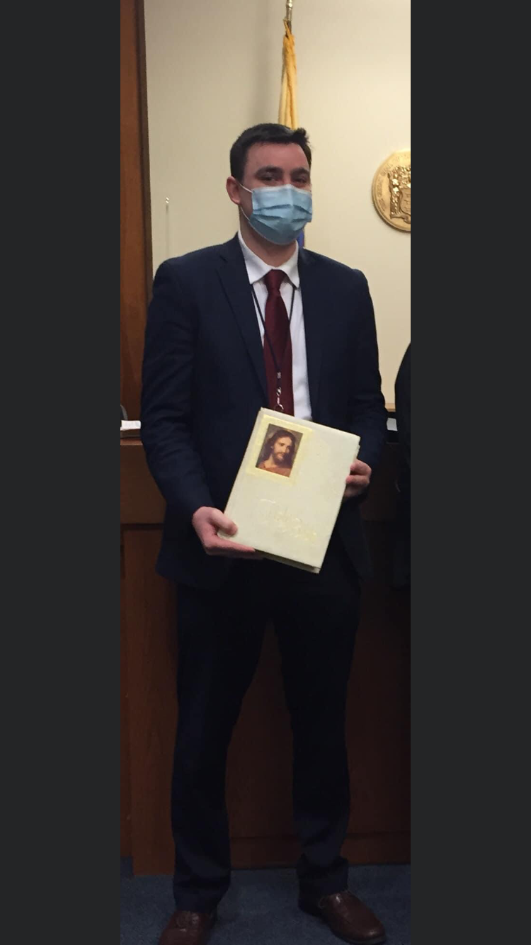 young man wearing mask and holding bible