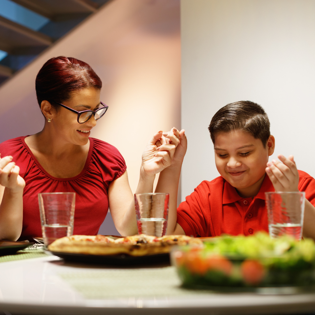Family praying before meal at dinner table with food and drinks
