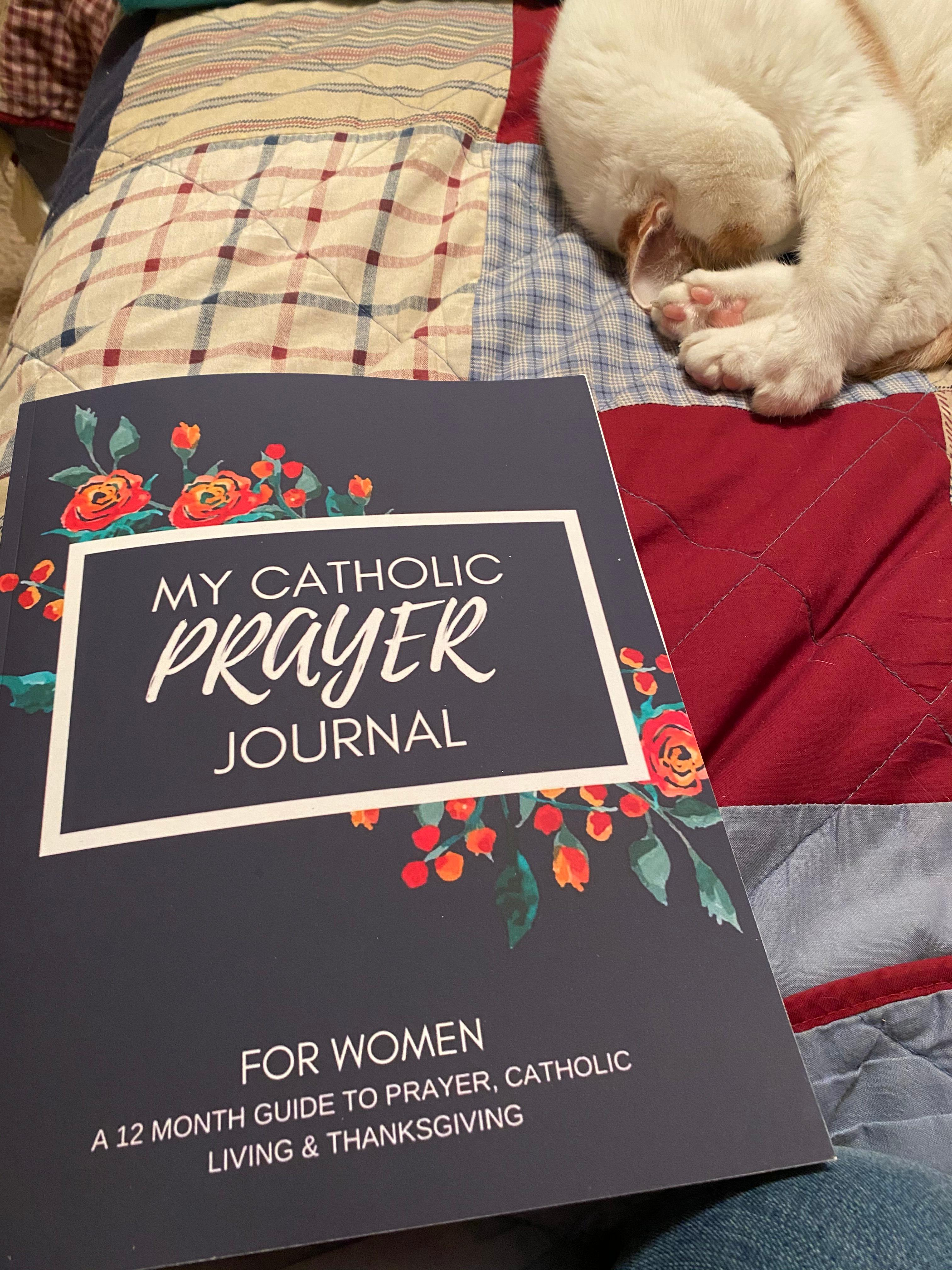Catholic Prayer Journal for women on red, white, and blue quilt, with white cat sleeping