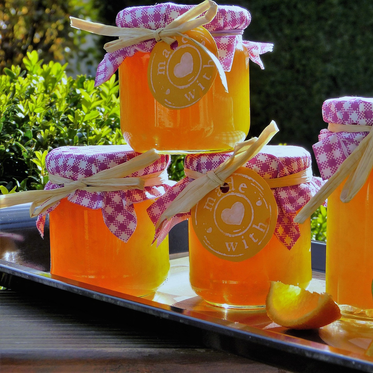 jars of orange marmalade with handcrafted lids and tags on tray with citrus slices
