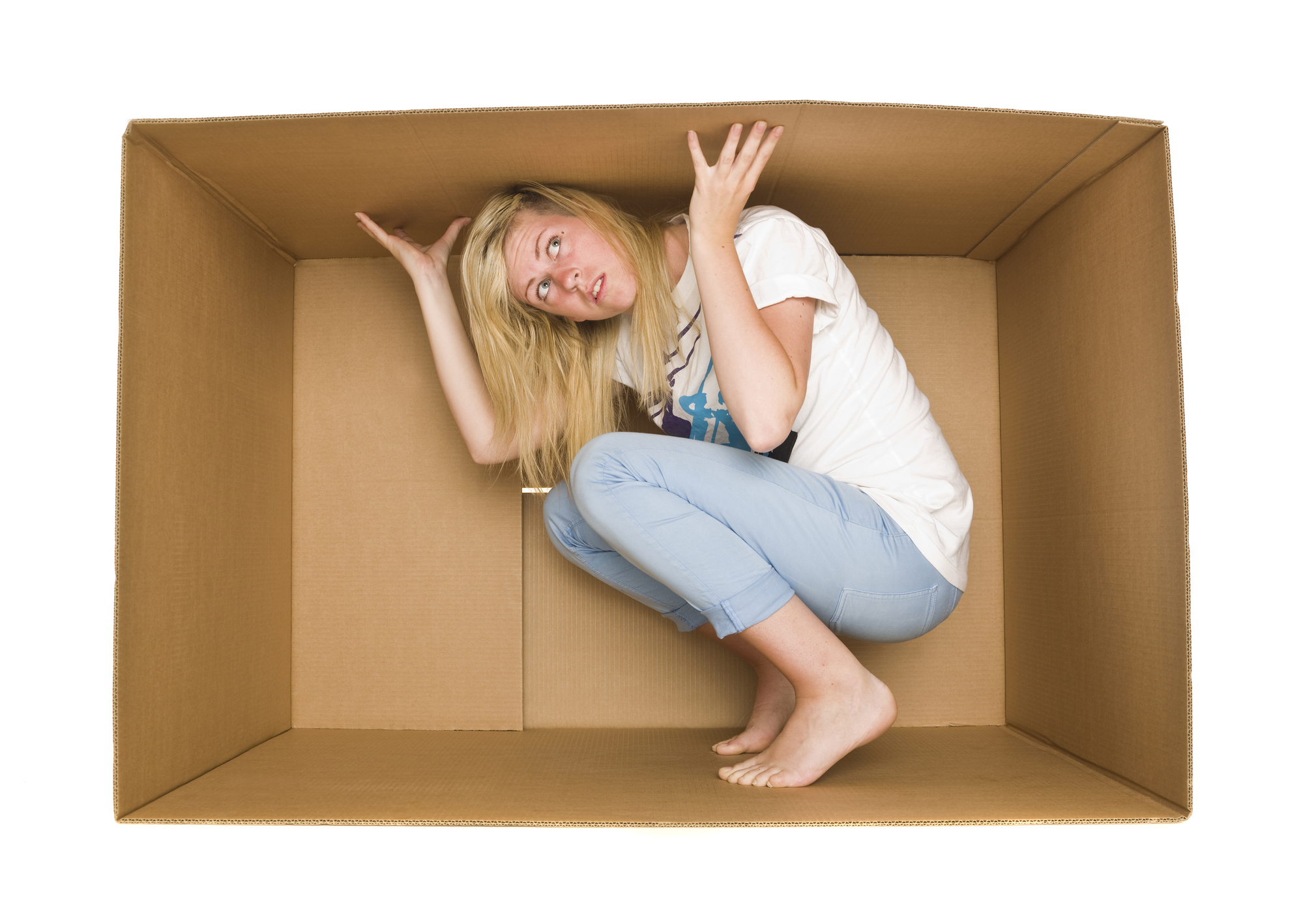 blond woman wearing jeans and white shirt, trapped inside cardboard box