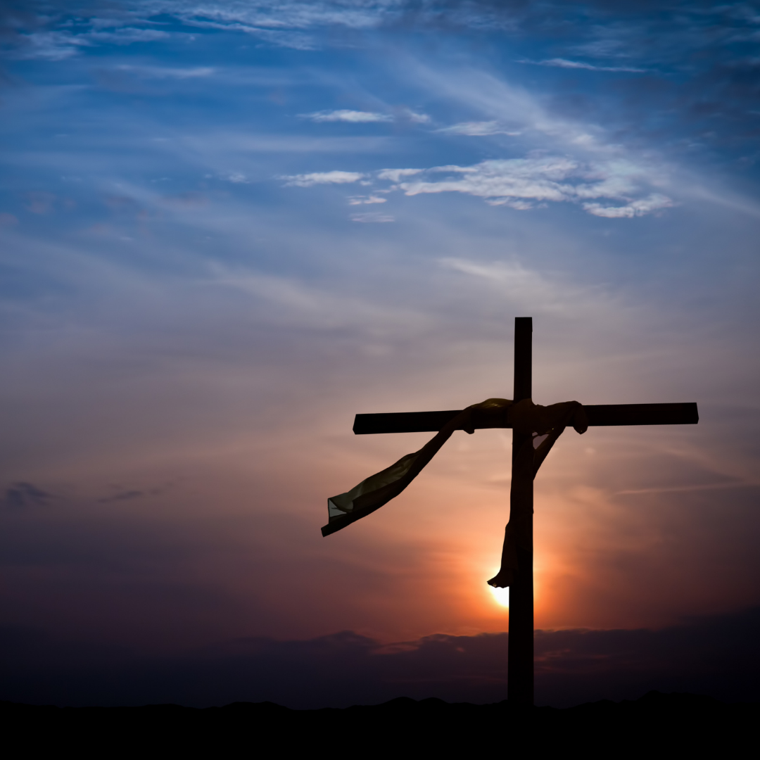 cross with fabric draped over it, sunset in background