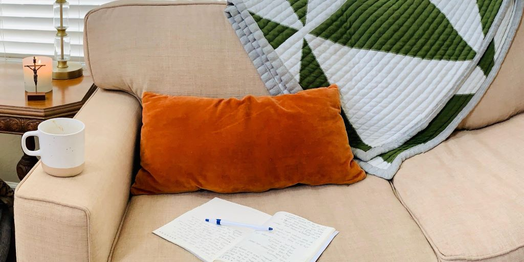 coffee mug, journal, pillow, and blanket on couch