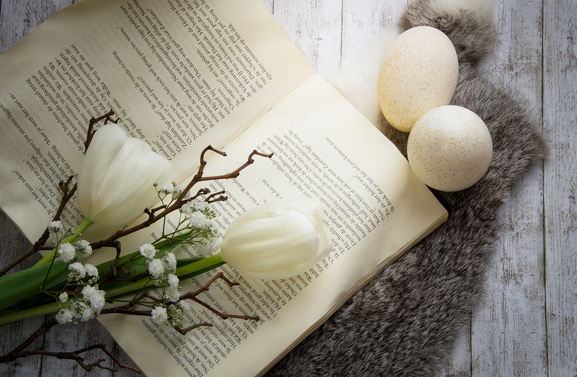 open book with tulips, baby's breath, and 2 speckled eggs