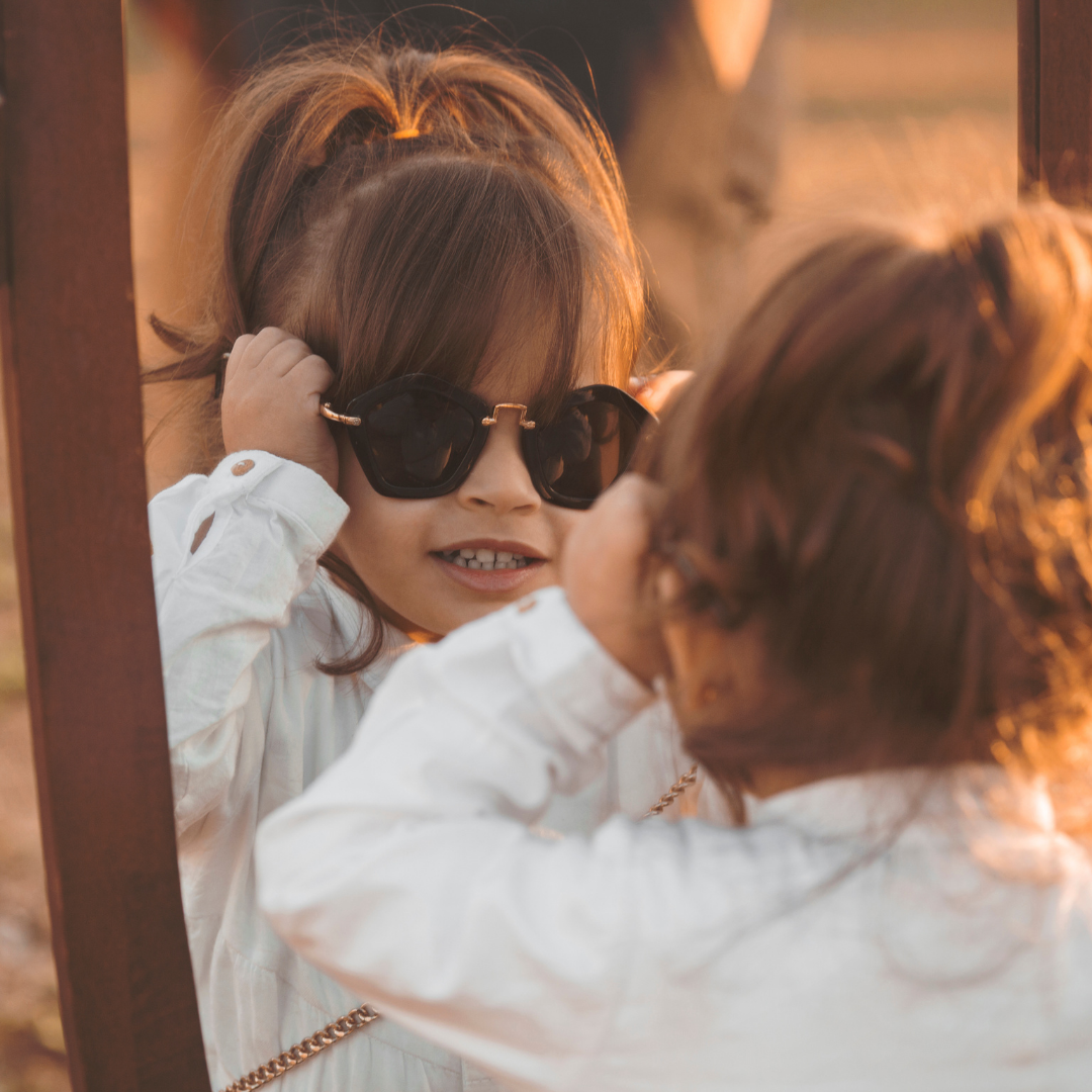 little girl trying on sunglasses in front of a mirror