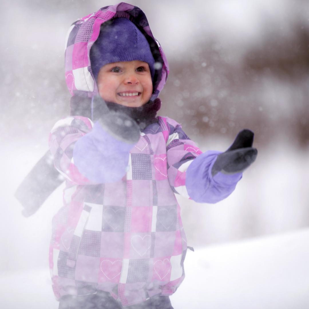 little girl wearing purple mittens in snowstorm