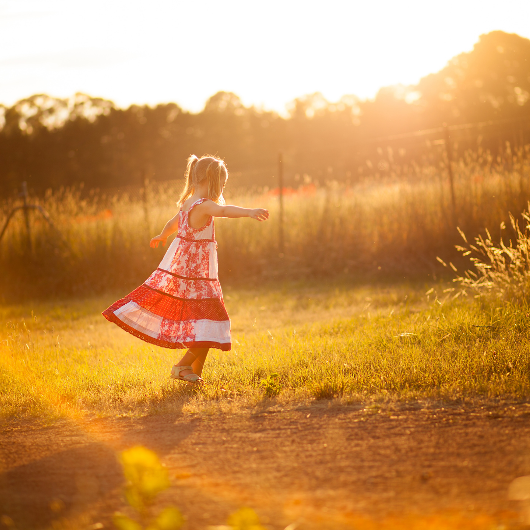 little girl twirling in a red and white dress