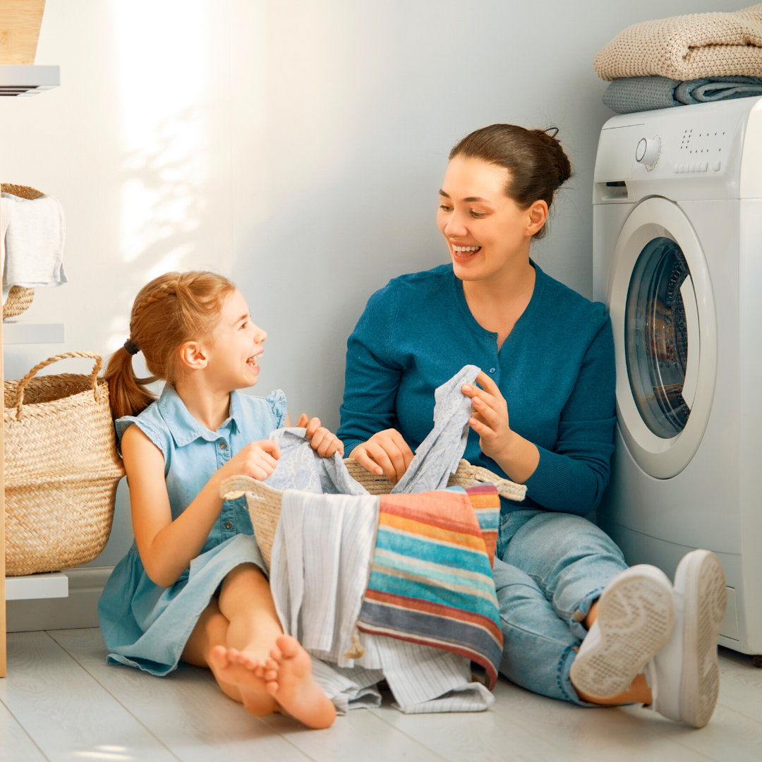 little girl folding laundry with mom
