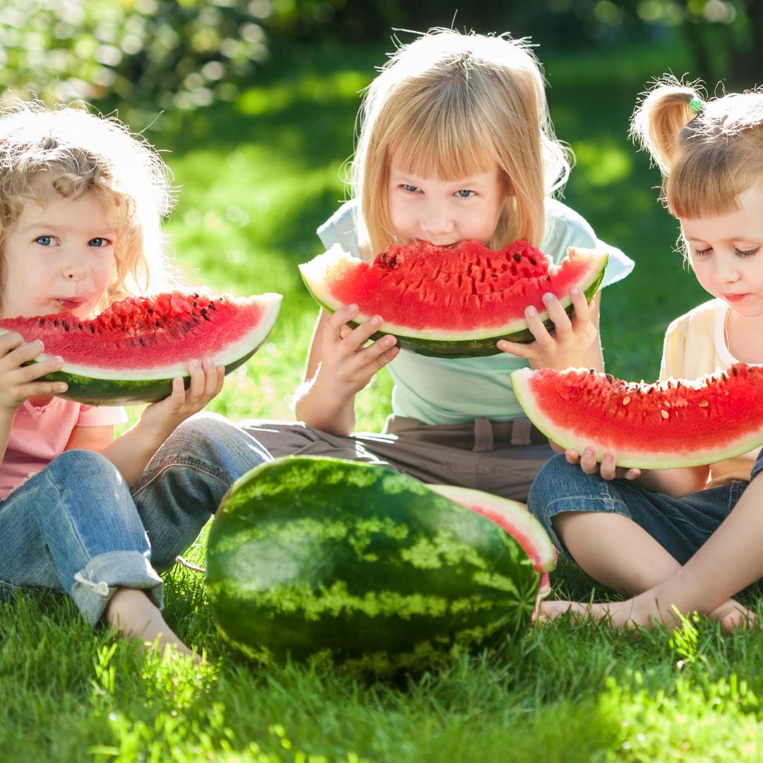 3 little girls eating giant watermelon slices outside