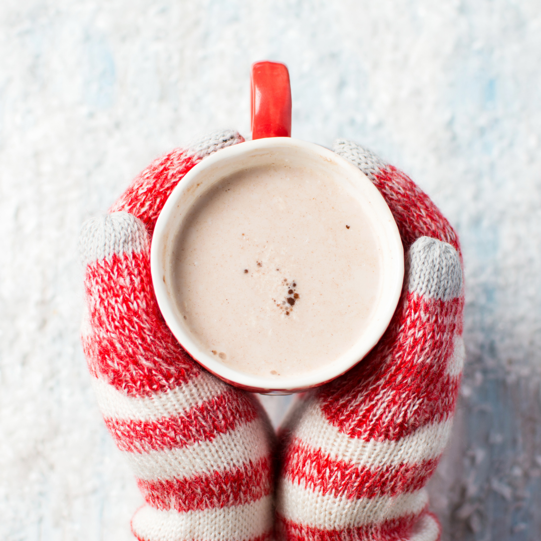 red and white mittened hands holding cup of cocoa