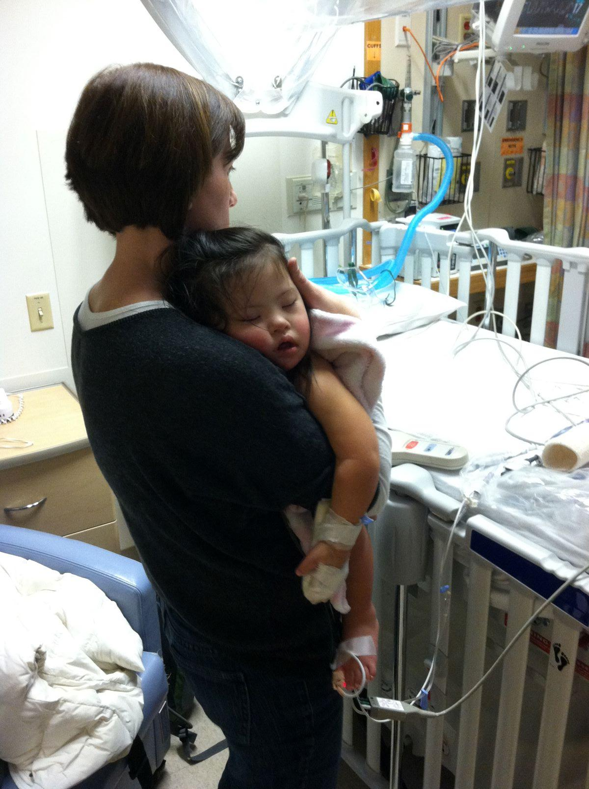 mother holding baby in hospital room