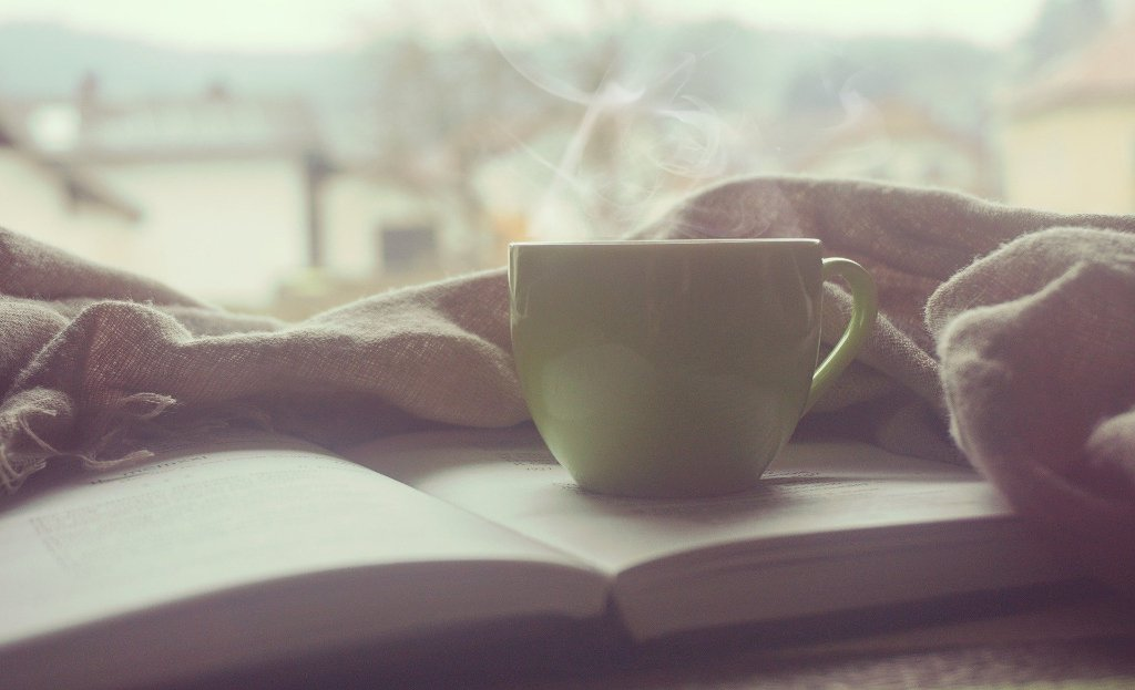 steaming coffee cup on top of open book and blanket