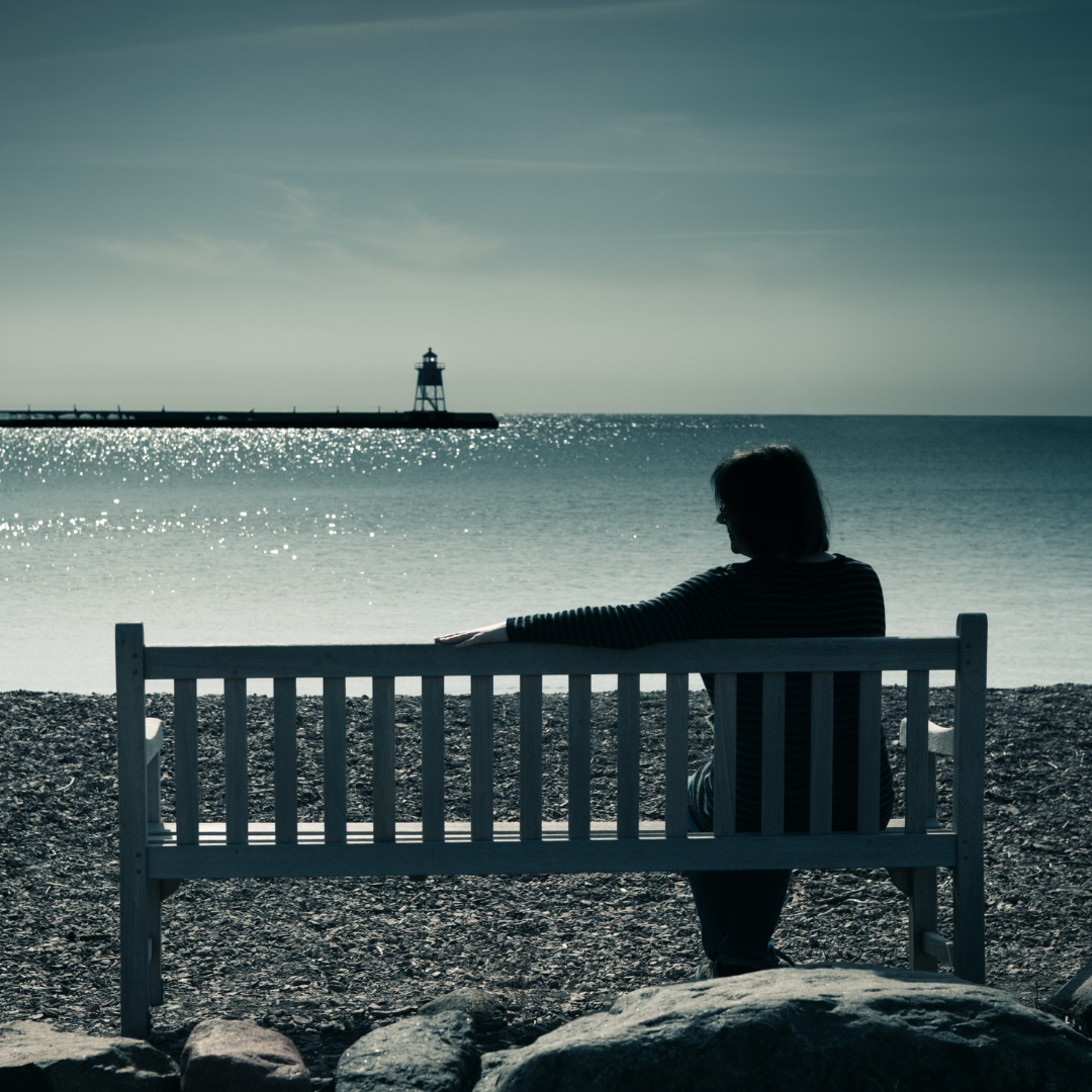 woman sitting alone on bench near shore, looking at lighthouse, stretching out her arm