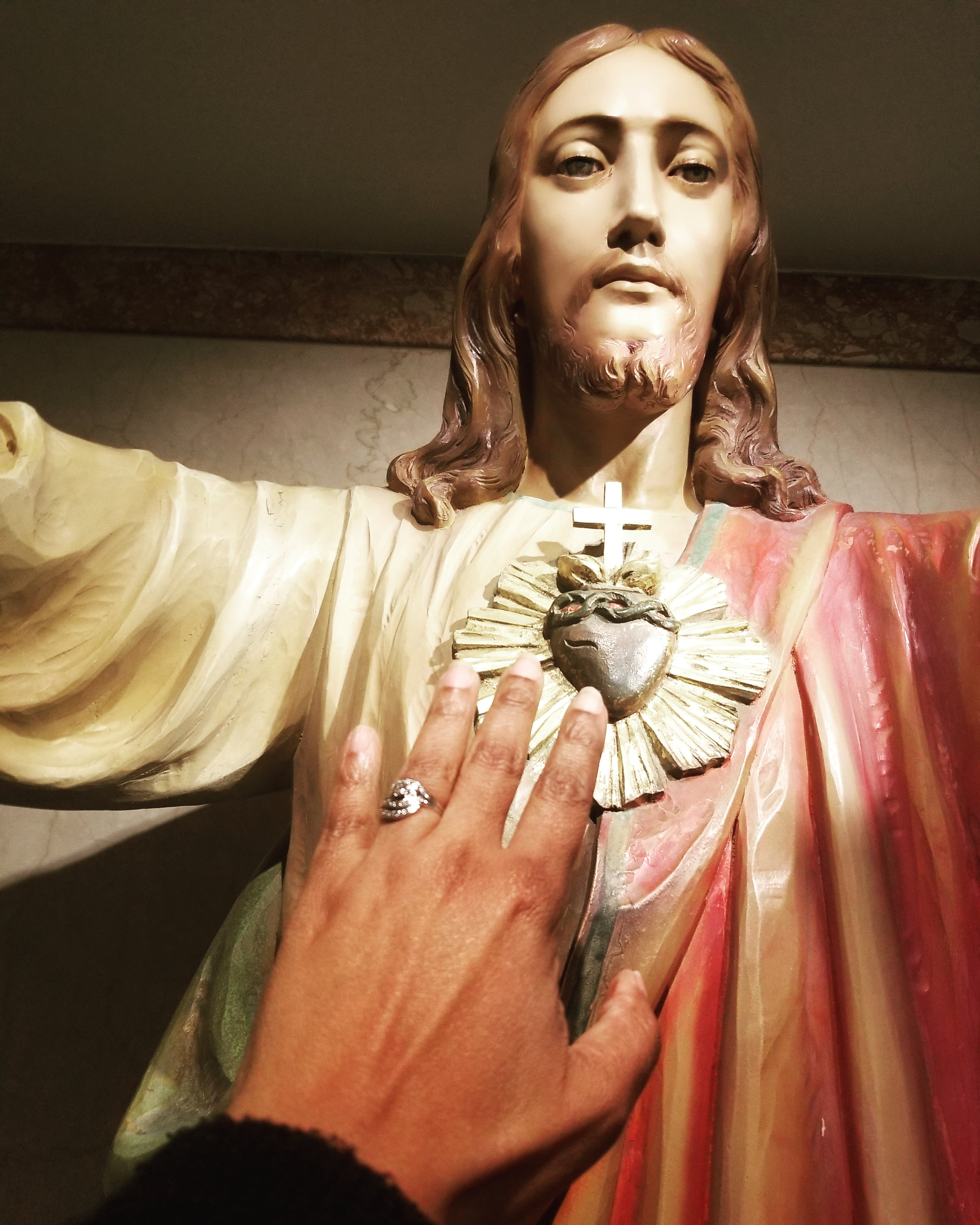 woman's hand touching Sacred Heart of Jesus statue