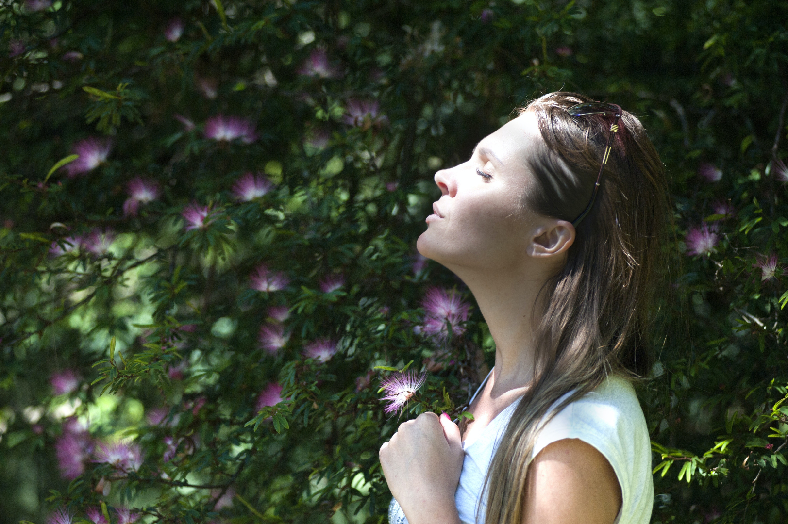 woman standing with eyes closed in front of tree with purple flowers