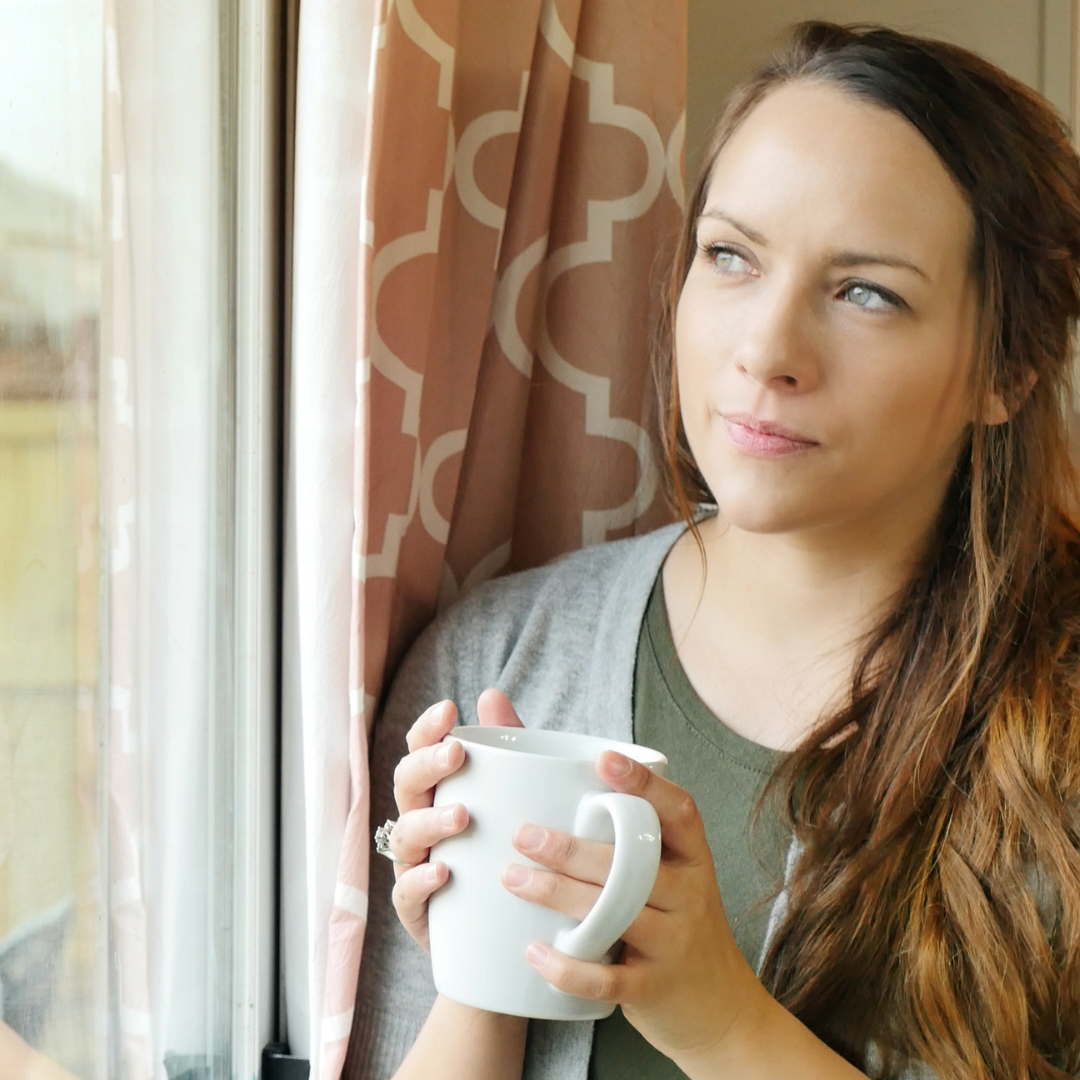 woman holding coffee cup and looking out the window