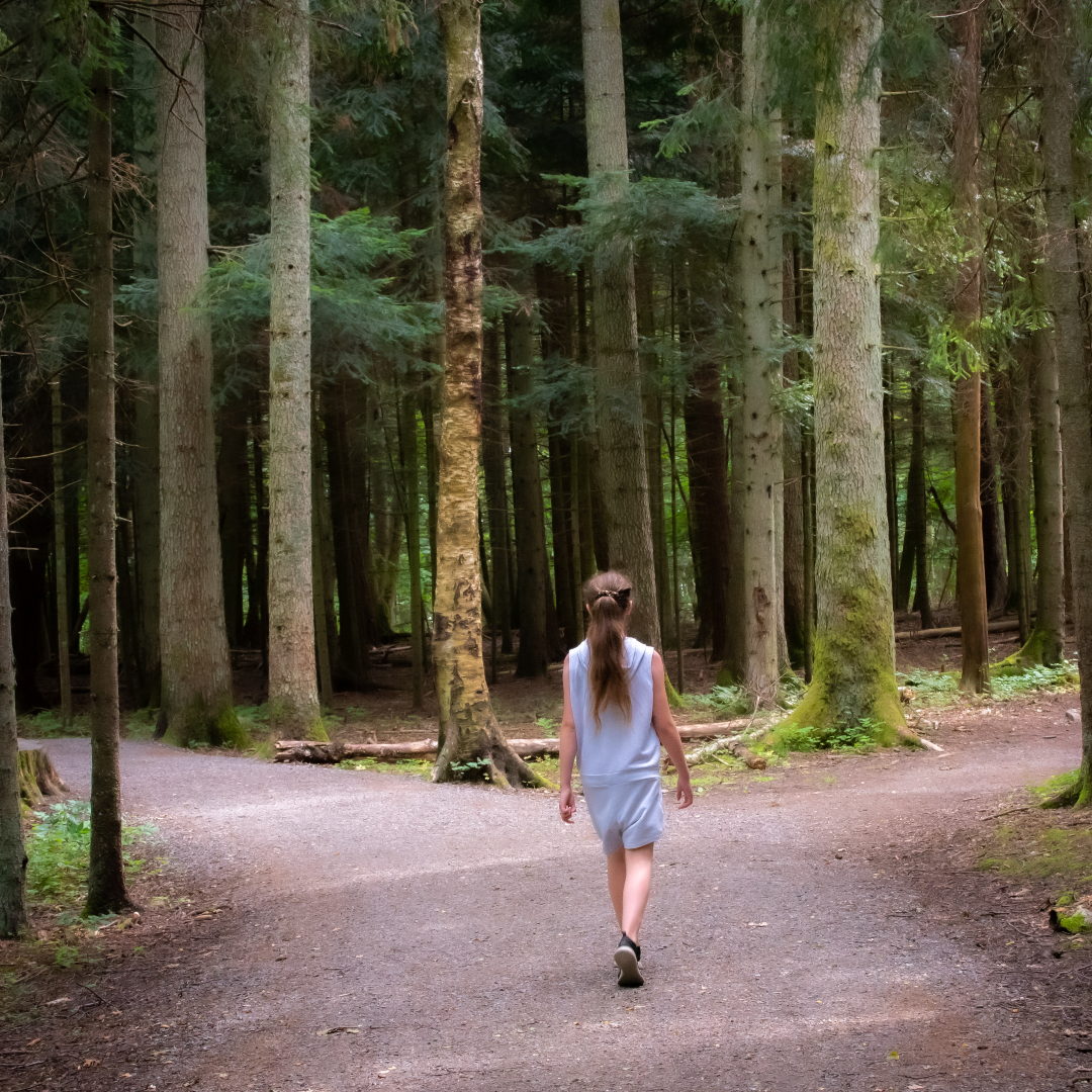 girl choosing a fork in the road in a forest path