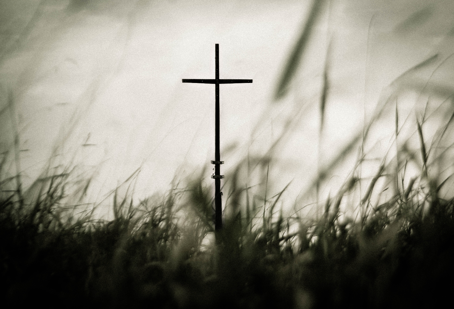 metal cross viewed from below with grass in the foreground