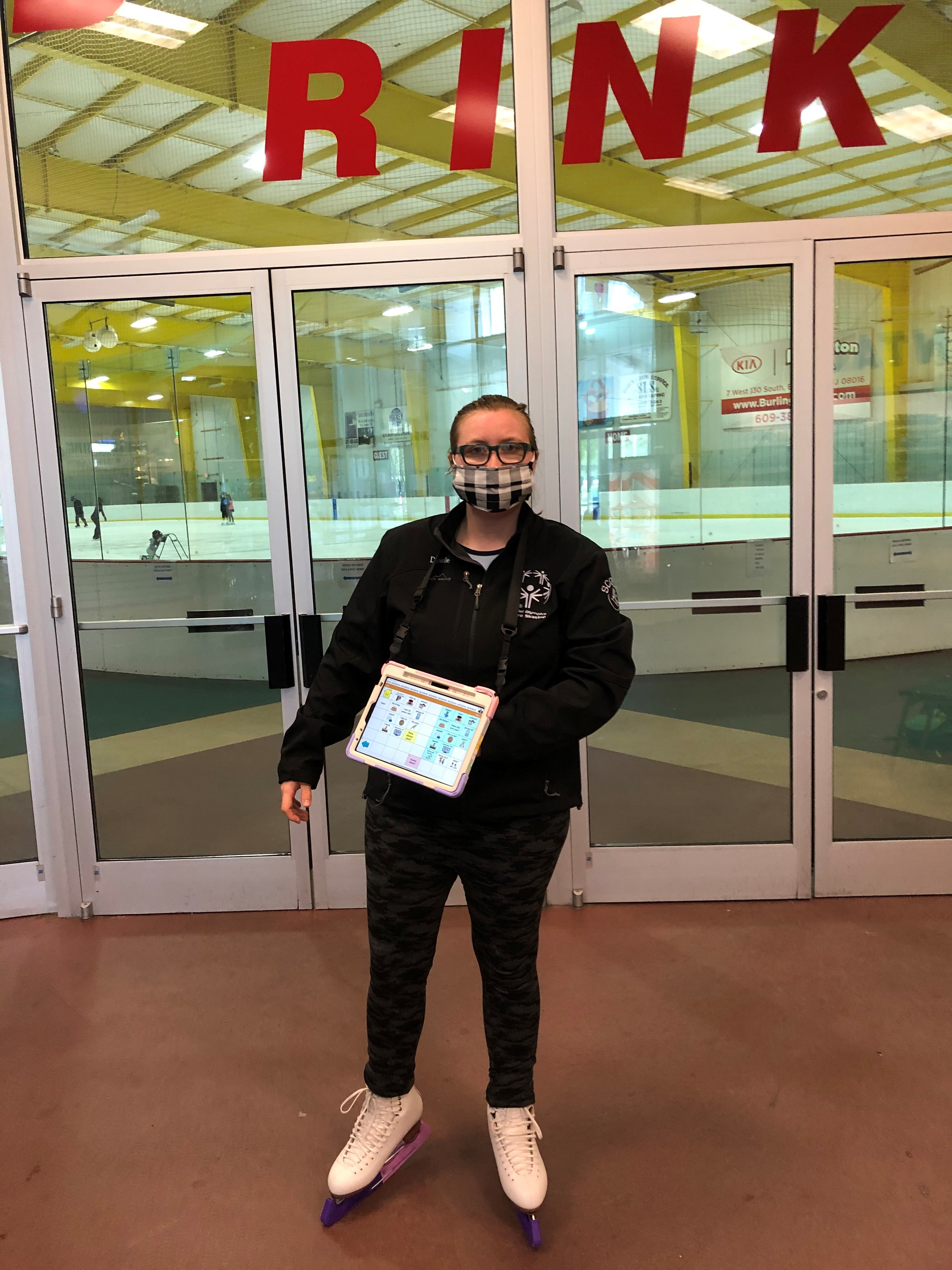 young woman with ipad and figure skates standing in front of ice skating rink