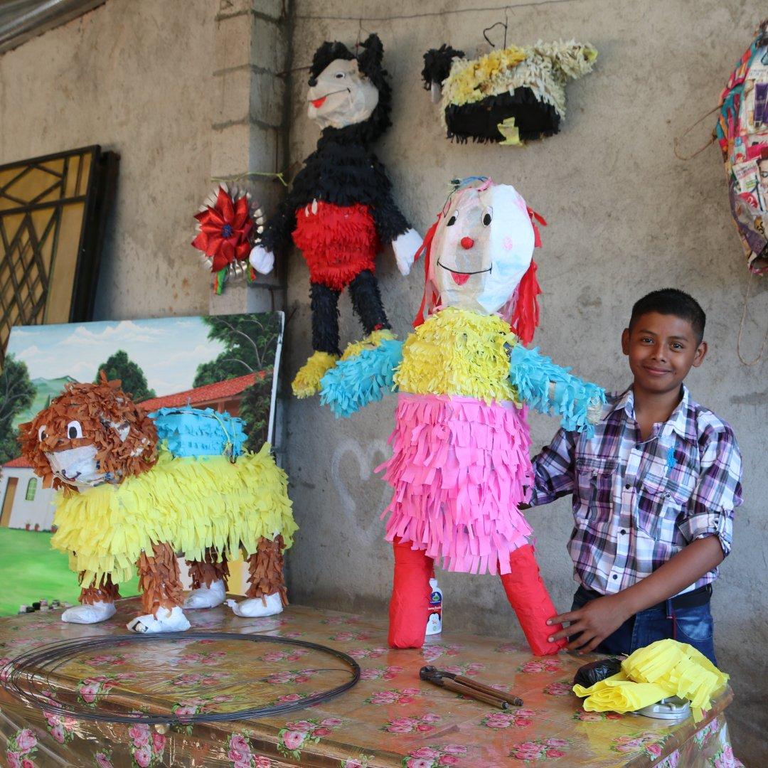 Emiliano shows off piñatas he made.