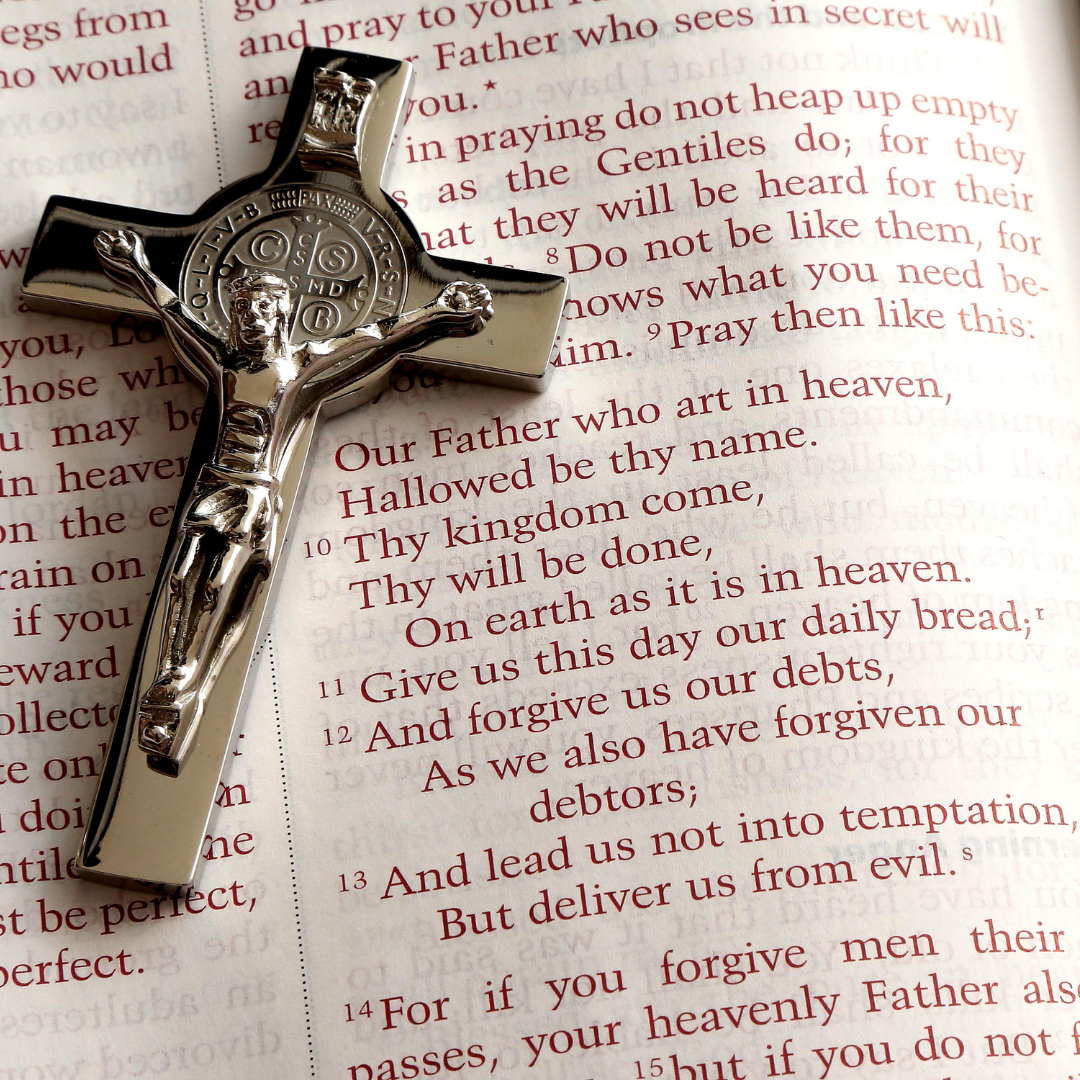 St. Benedict cross over Bible page with Lord's prayer