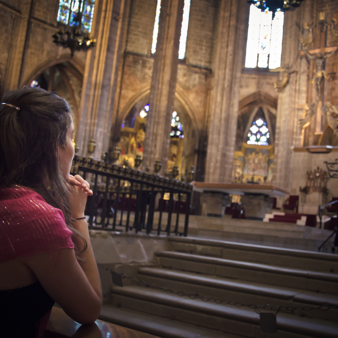 woman praying in front of crucifix at church