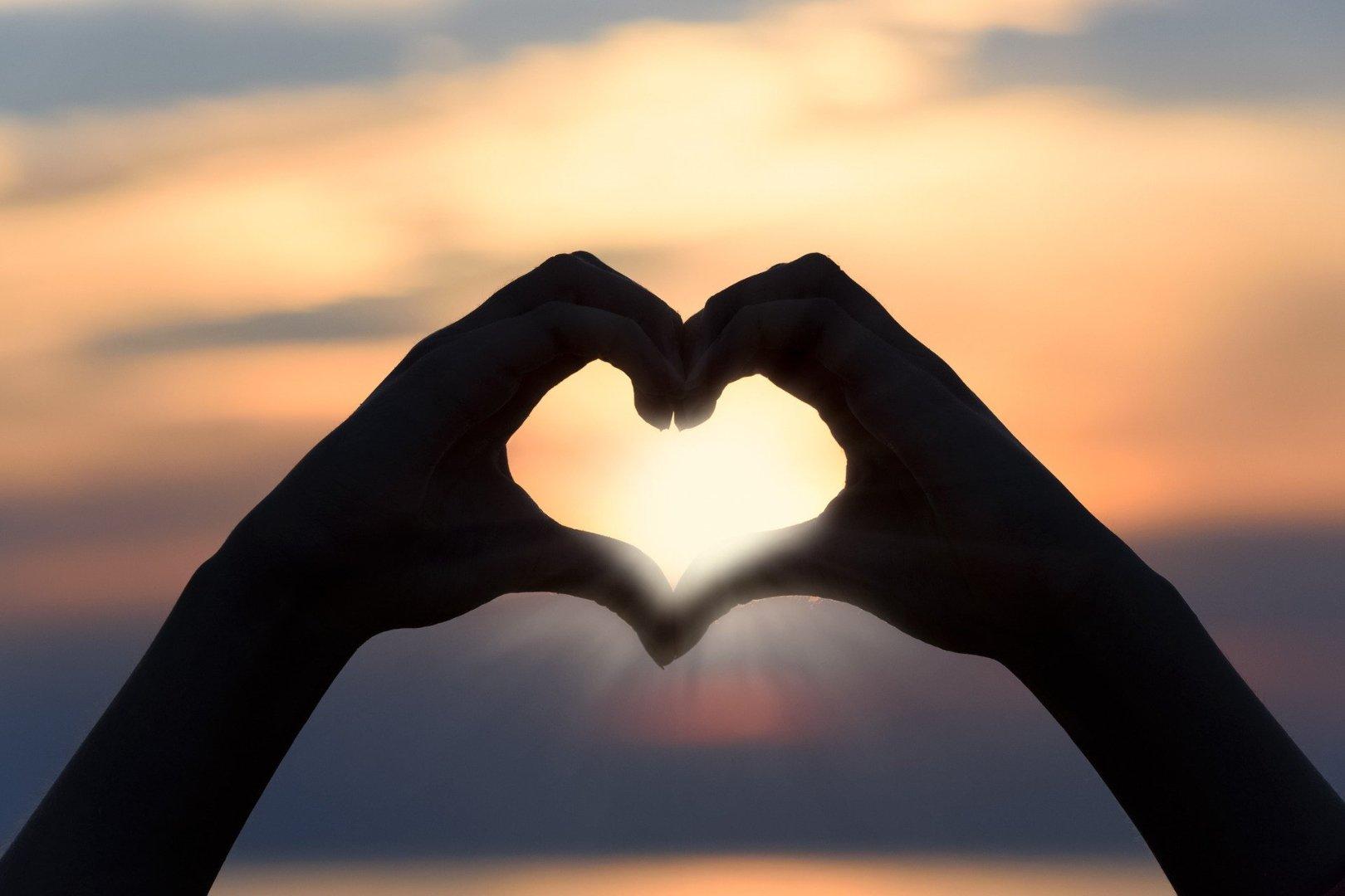 sunset viewed through 2 hands forming a heart