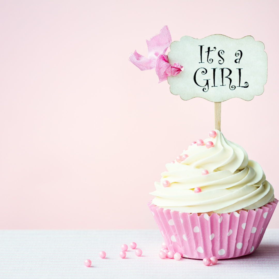 """pink and white cupcake with """"it's a girl"""" decoration"""