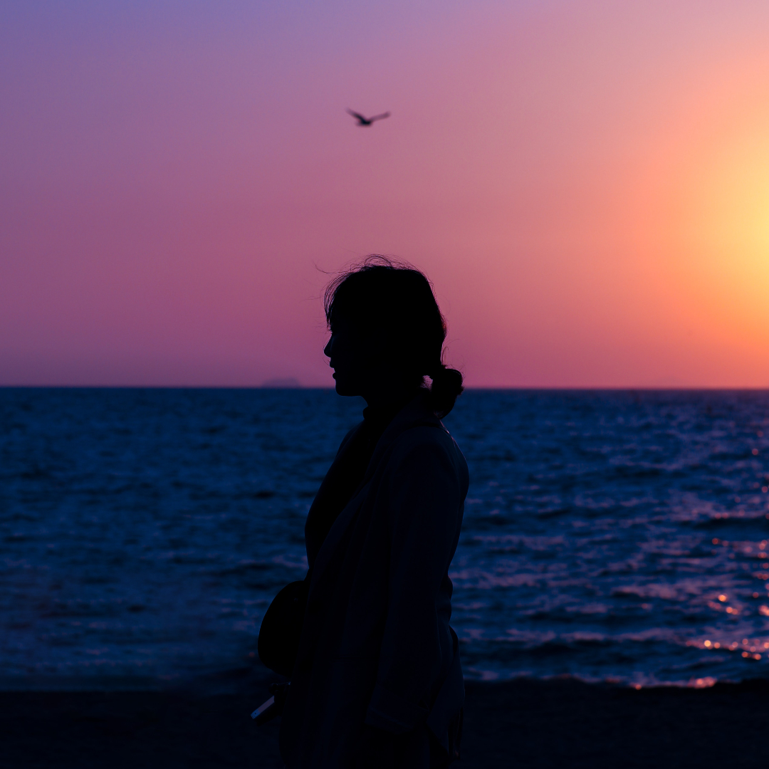 woman silhouetted against ocean sunset