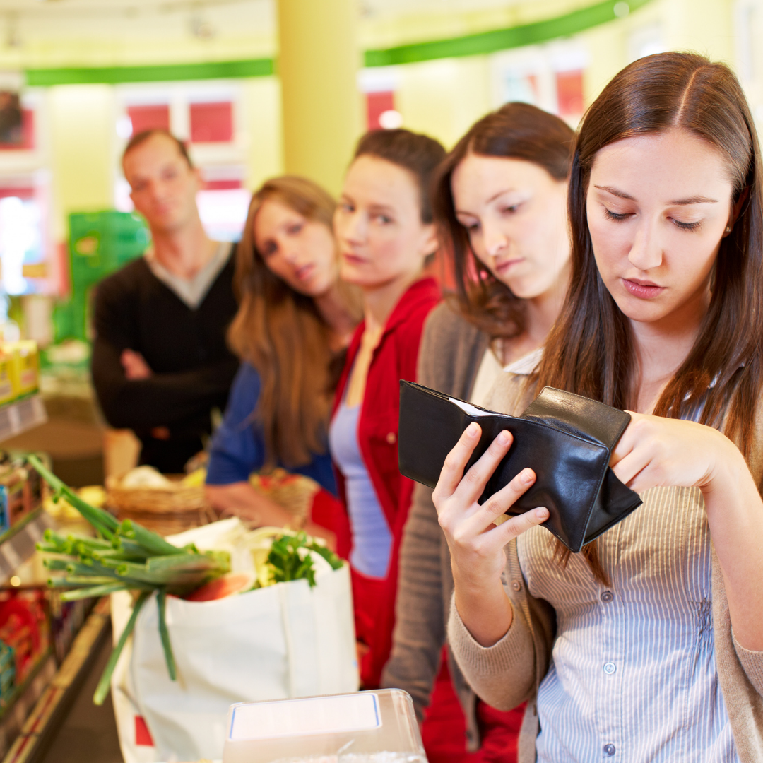 people standing impatiently in line behind woman looking through wallet