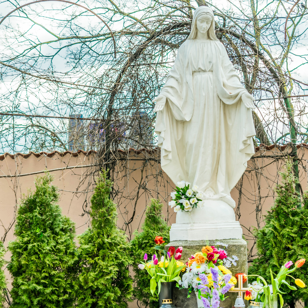 outdoor statue of Mary in garden with flowers at her feet