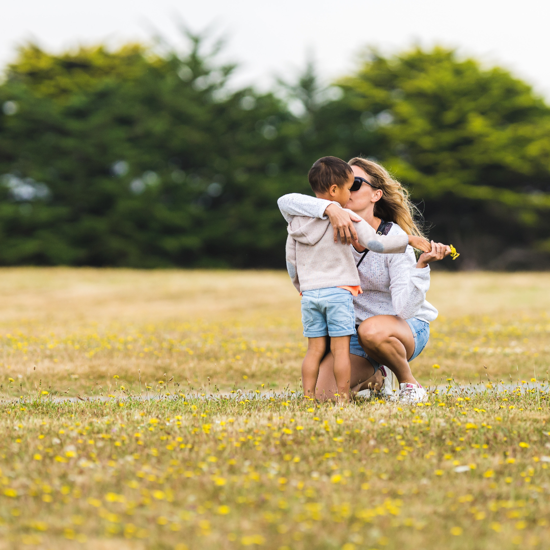 mom kissing little boy after he gives her a handful of dandelions