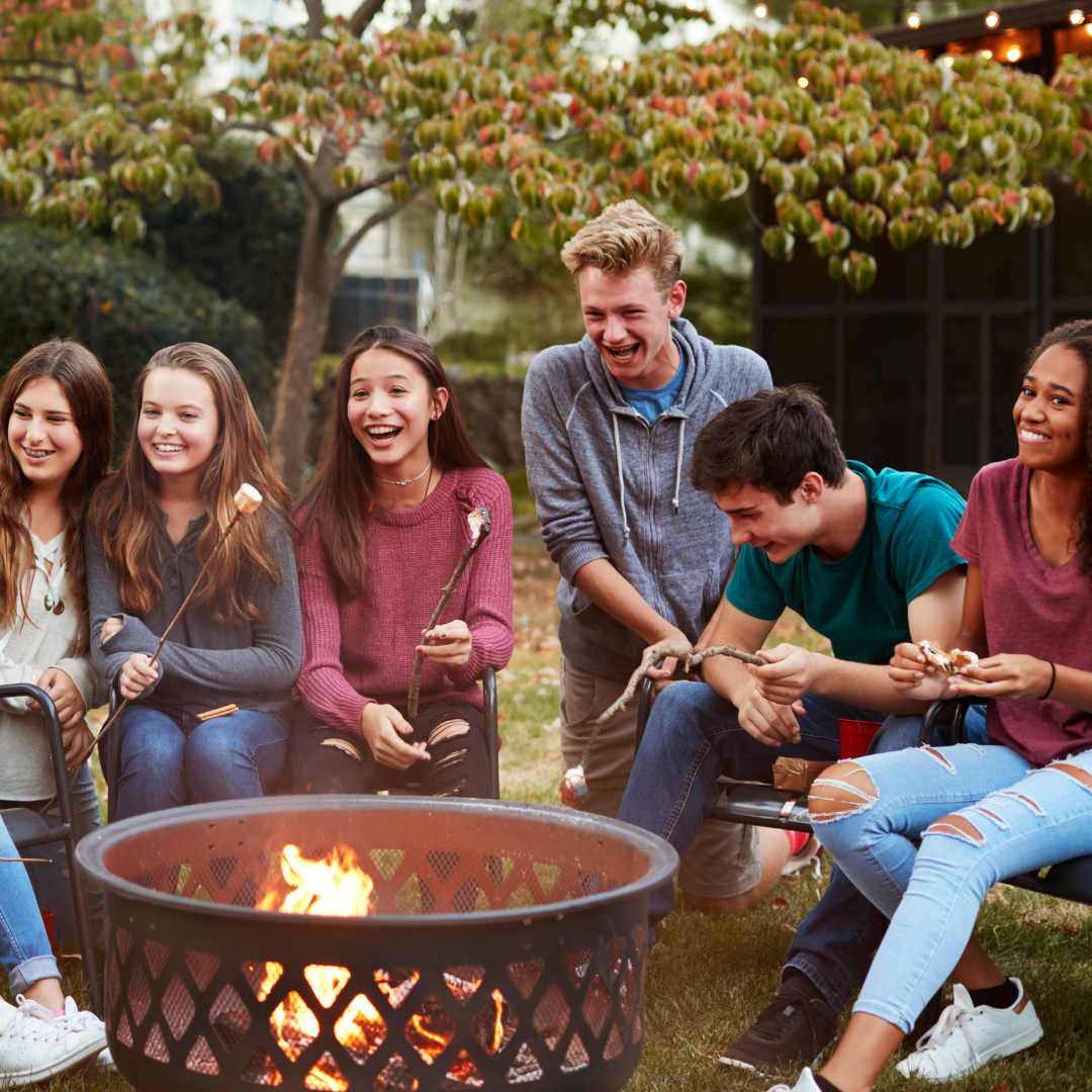 friends laughing around a fire pit