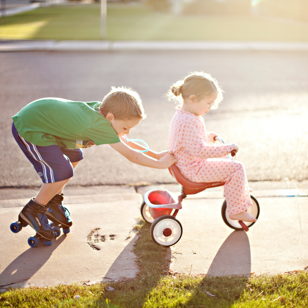 big brother on roller skates pushing little sister on tricycle