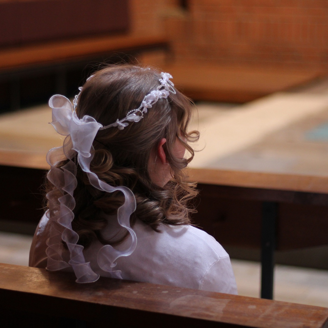 girl dressed for First Communion, sitting alone in a church