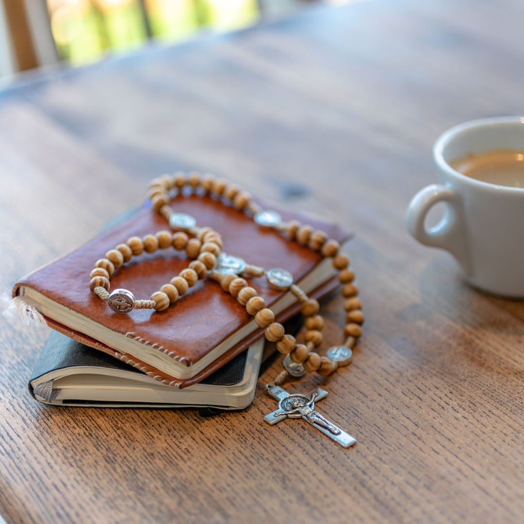 Rosary with Bible and prayer book and coffee cup
