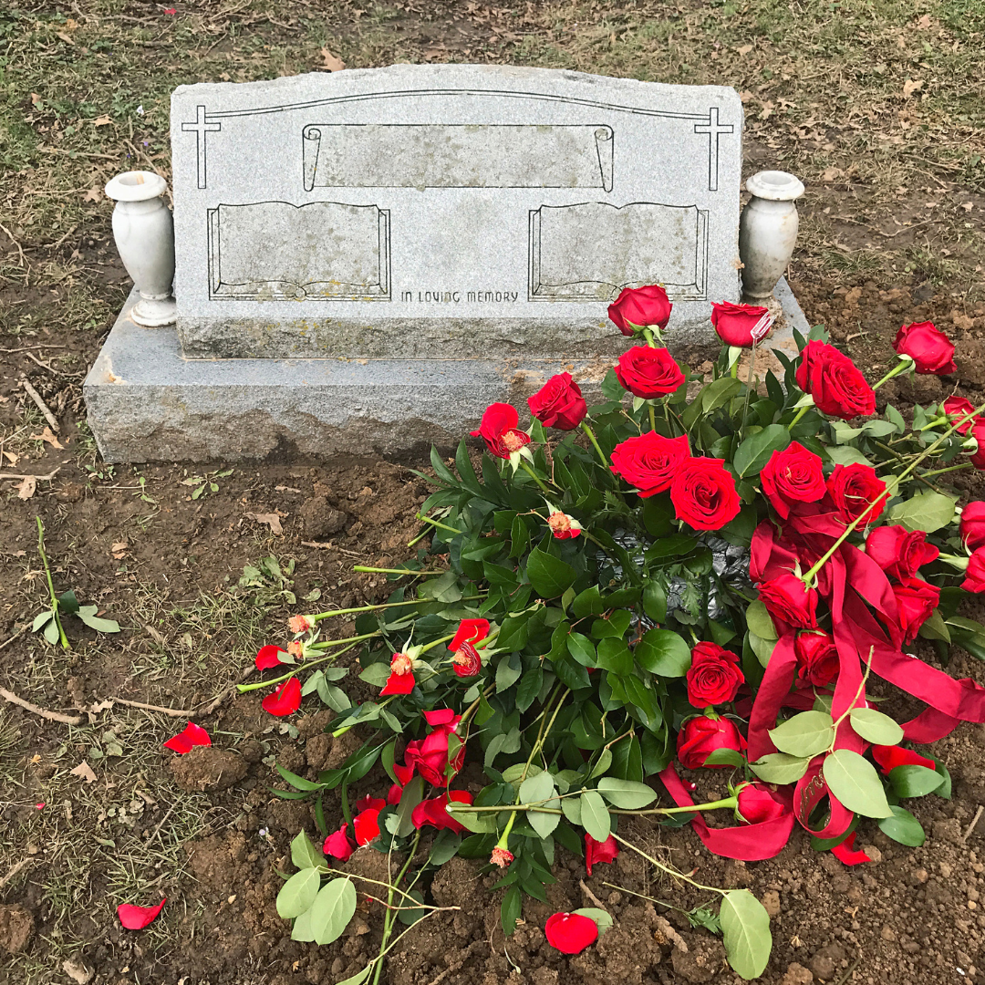 unmarked gravestone with fresh red roses