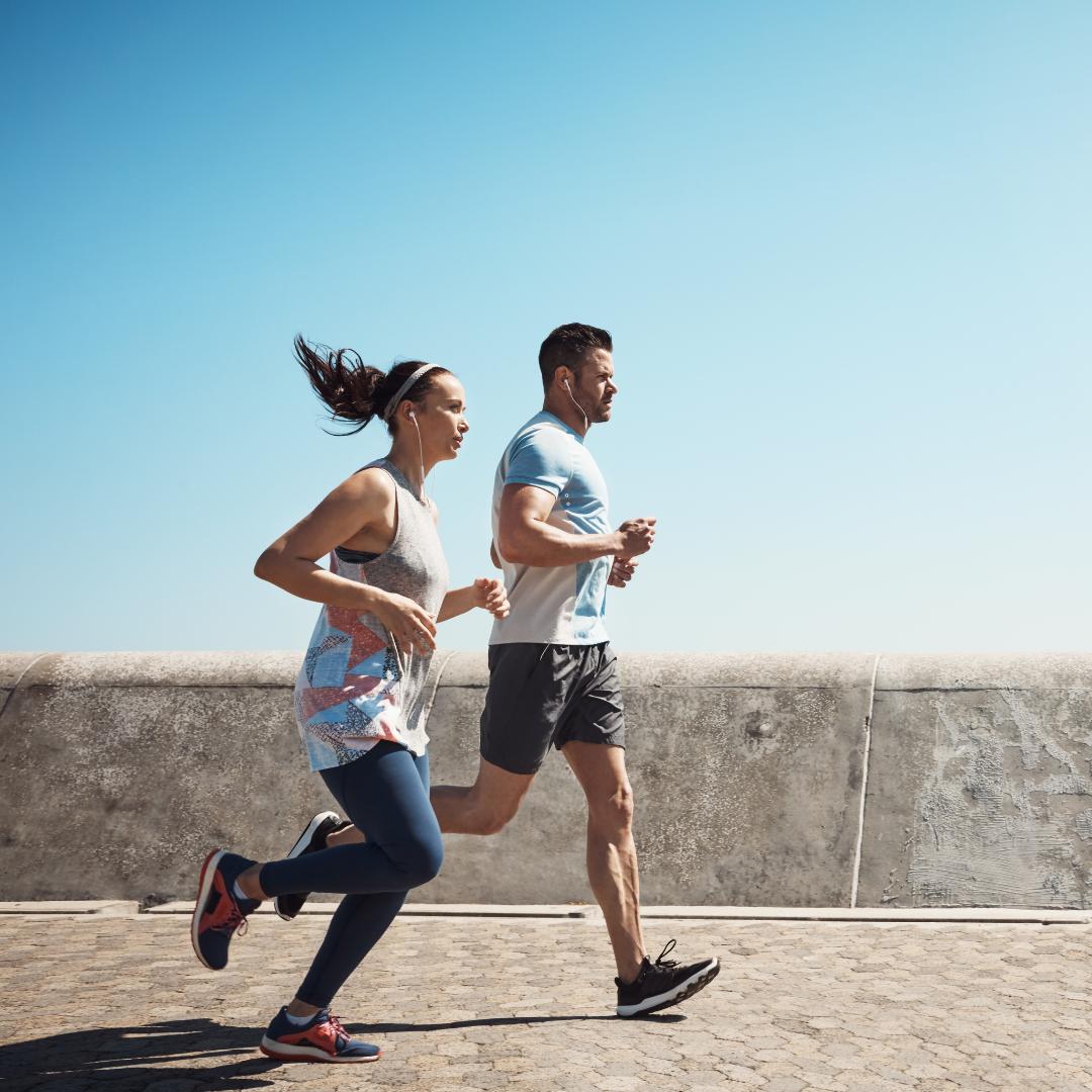 woman and man running on sidewalk