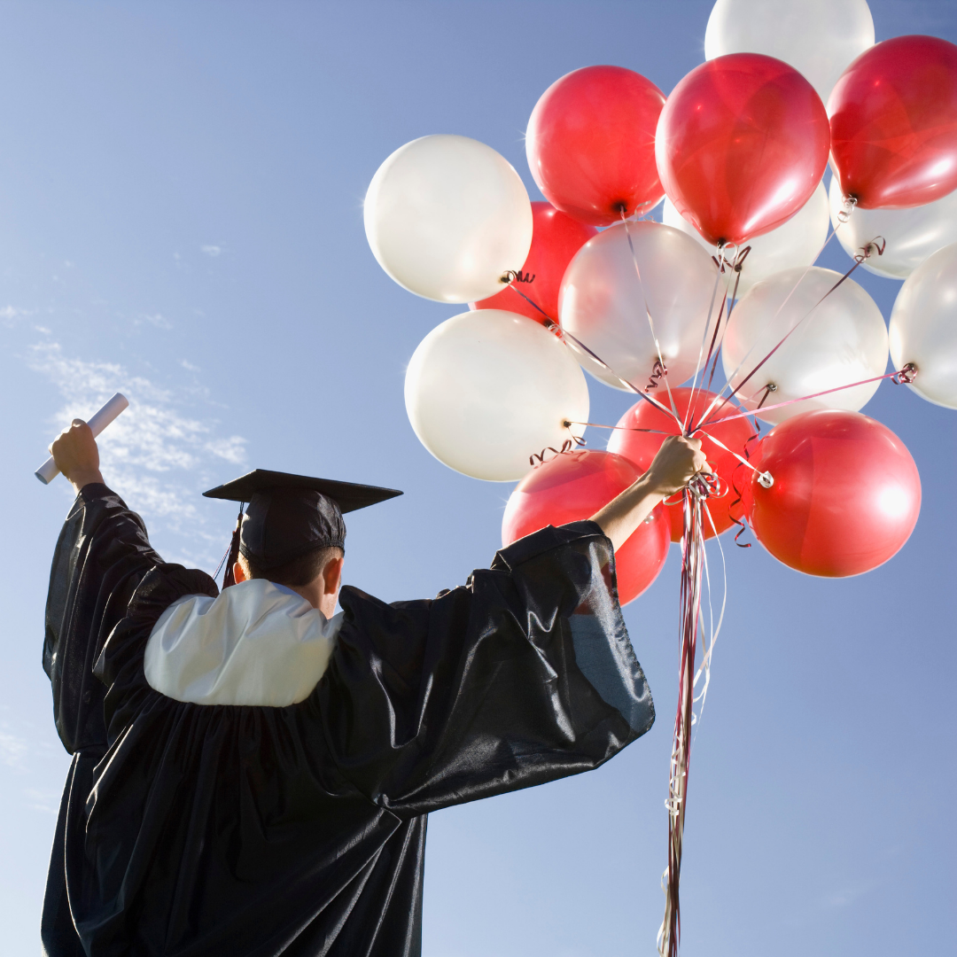 graduate holding diploma and a bunch of red and white balloons