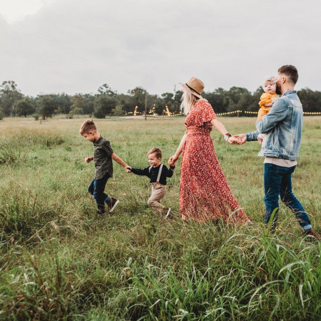 little boy leading family through a field