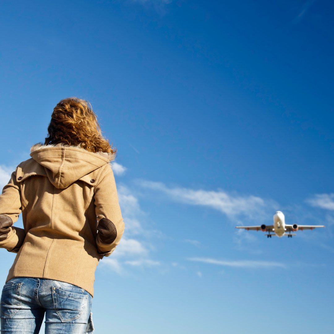 woman looking at airplane flying overhead