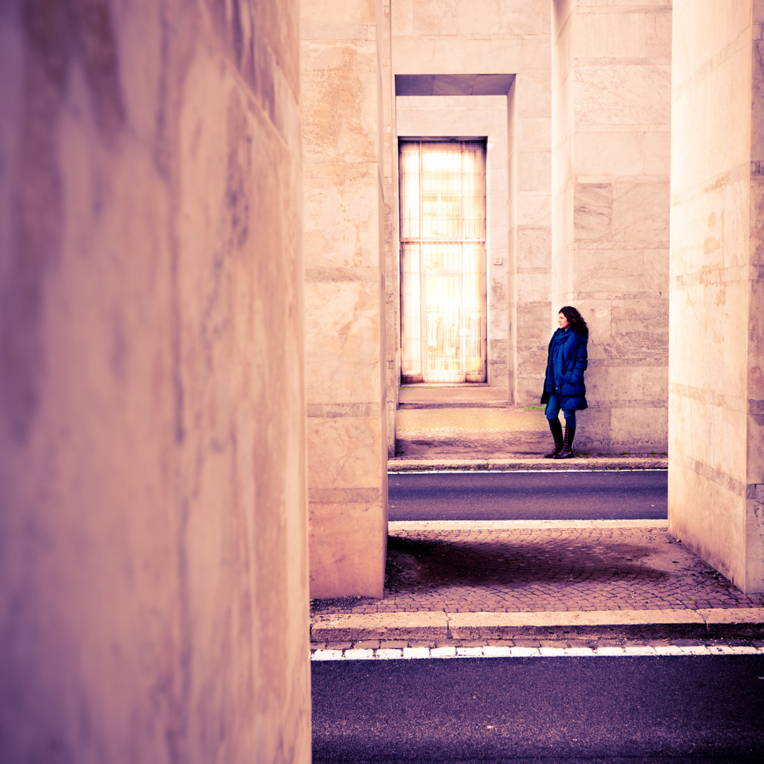 woman standing alone near a large building
