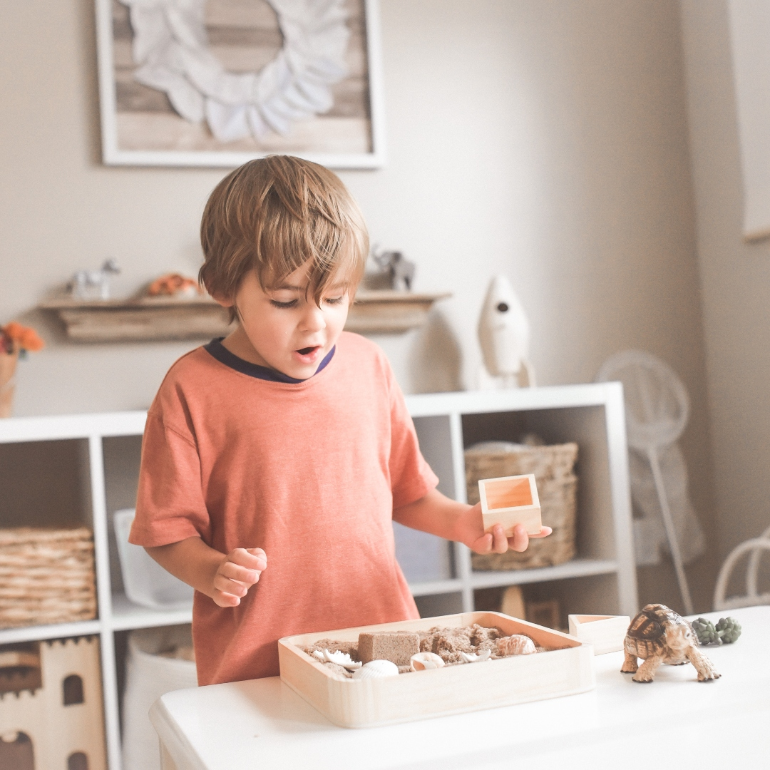 little boy playing with blocks and toy animals