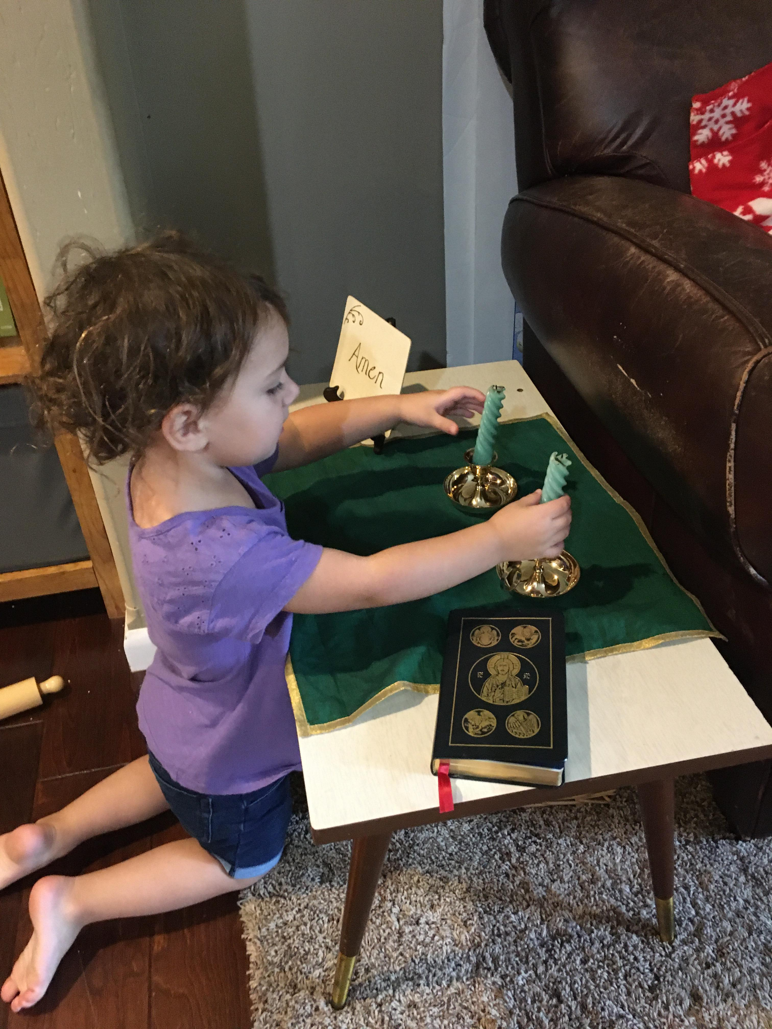 toddler reaching for candles at prayer table
