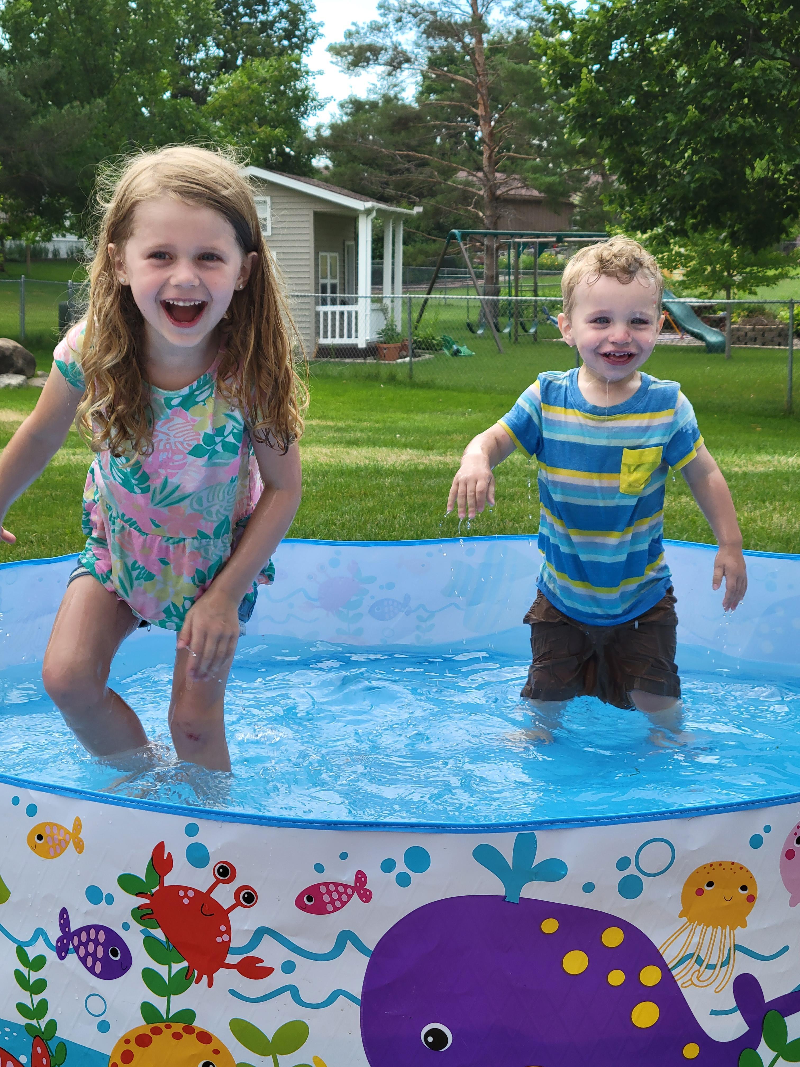 small children playing in backyard pool