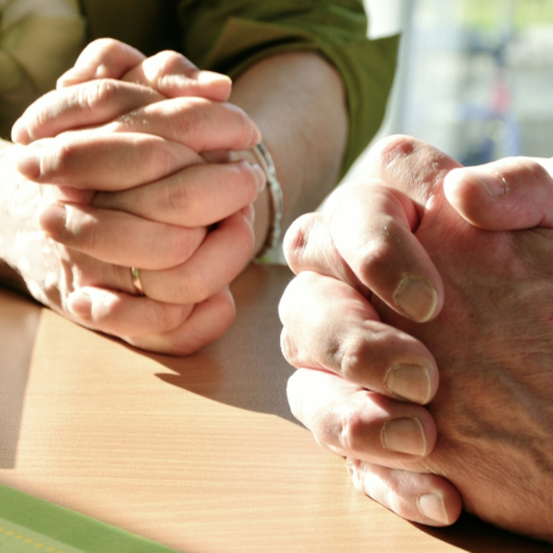 woman and man with hands folded in prayer